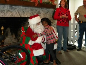 "With White Springs' mayor Dr. Helen Miller looking on, hugs and gifts are exchanged at ""Breakfast With Santa."""